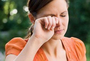 Девушка трет глаз рукой
