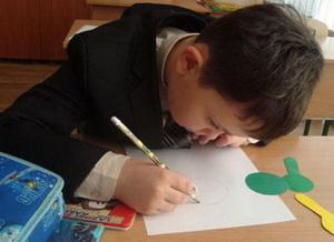 Мальчик за партой рисует
