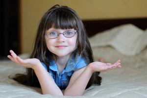 Девочка в очках на кровати